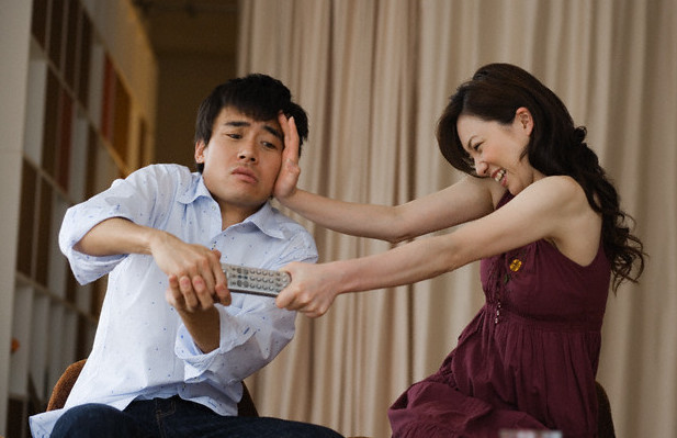 Couple Fighting Over Remote Control --- Image by © Corbis