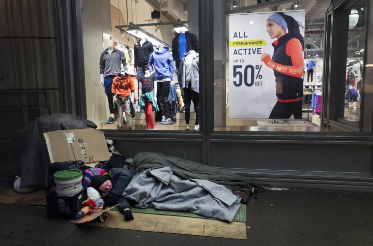 A homeless person sleeps under a blanket outside an Old Navy store window display, Wednesday, Jan. 11, 2017. (AP Photo/Mark Lennihan)