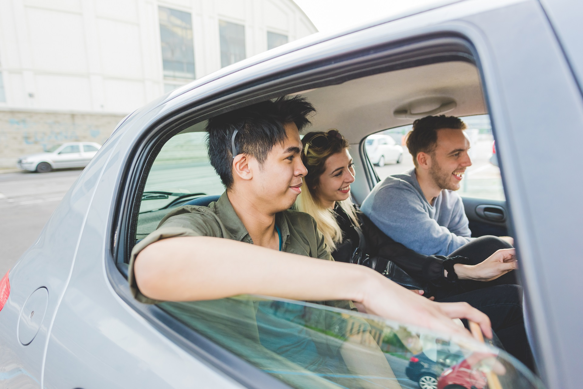 Three-young-people-sharing-the-back-seat-of-a-car-carpooling-their-way-to-work-this-is-carpooling-rather-than-car-sharing-what-is-carpool
