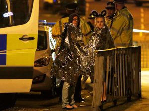 Two women wrapped in thermal blankets stand near the Manchester Arena, where U.S. singer Ariana Grande had been performing, in Manchester, northern England, Britain, May 23, 2017. REUTERS/Andrew Yates - RTX373KD