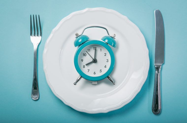 Intermittent fastin concept - empty plate on blue background, copy space